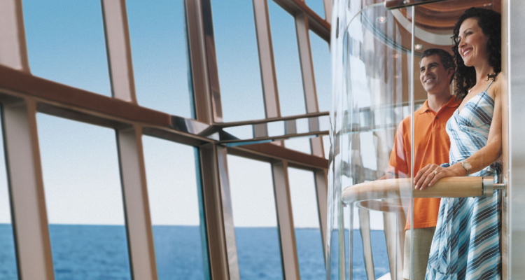 Couple in glass elevator over looking ocean waters from cruise ship