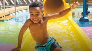A male toddler smiling having fun in the water park onboard Royal Caribbean cruises