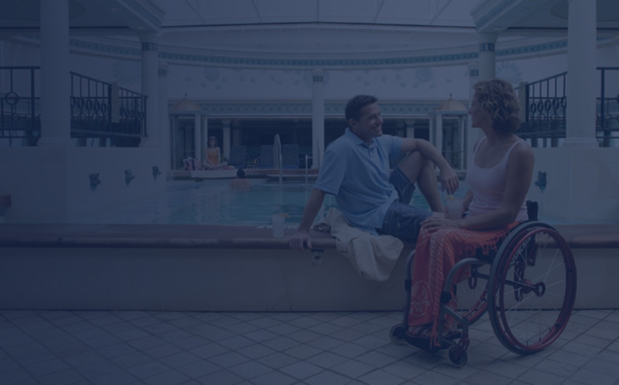 A couple in a wheelchair having a romantic moment by the indoor pool on our cruise ships