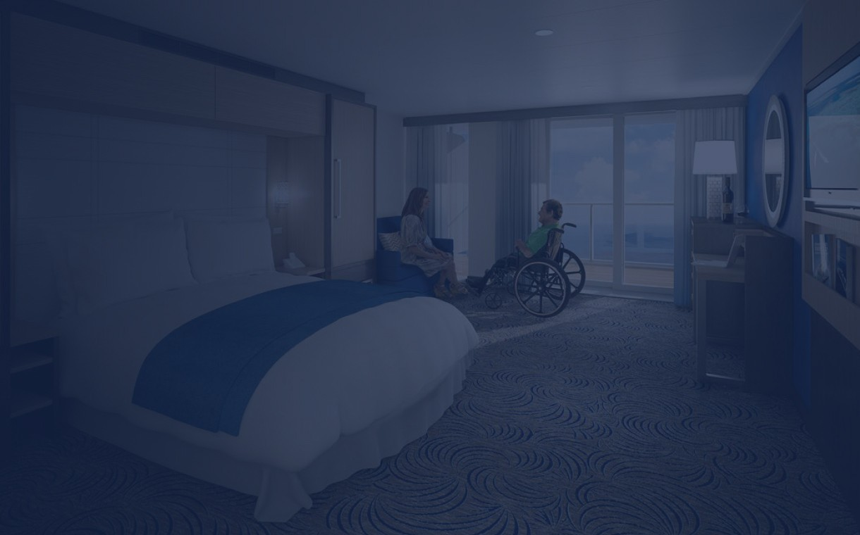 A gentleman on a wheelchair with his wife in his stateroom onboard a ship