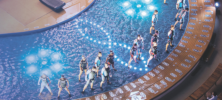 An aerial view of a group of performers over water during an Aqua Theater cruise show.