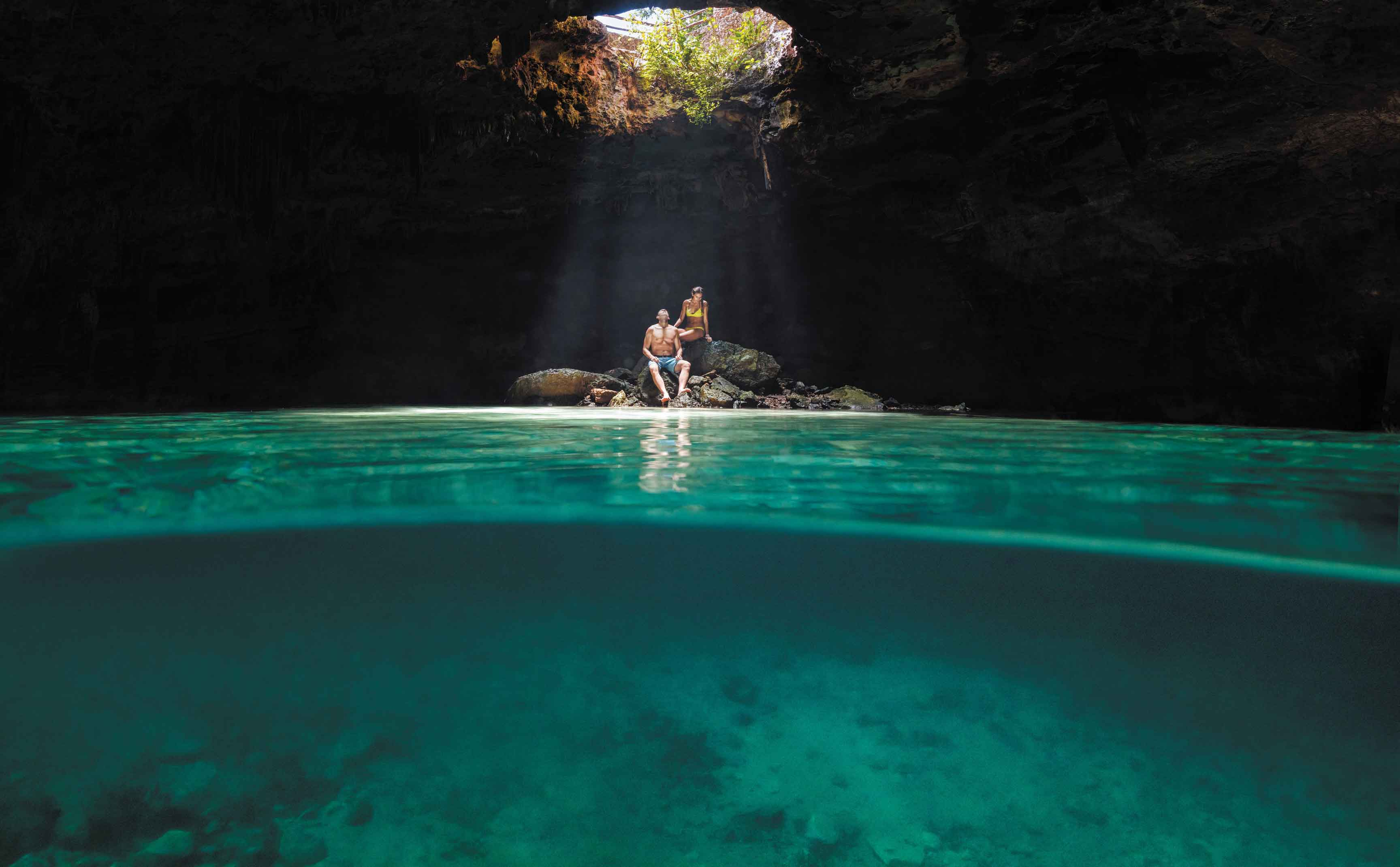 Romantic couple on their cruise vacation inside of a cenote or underwater cave sitting on rocks in Cozumel, Mexico