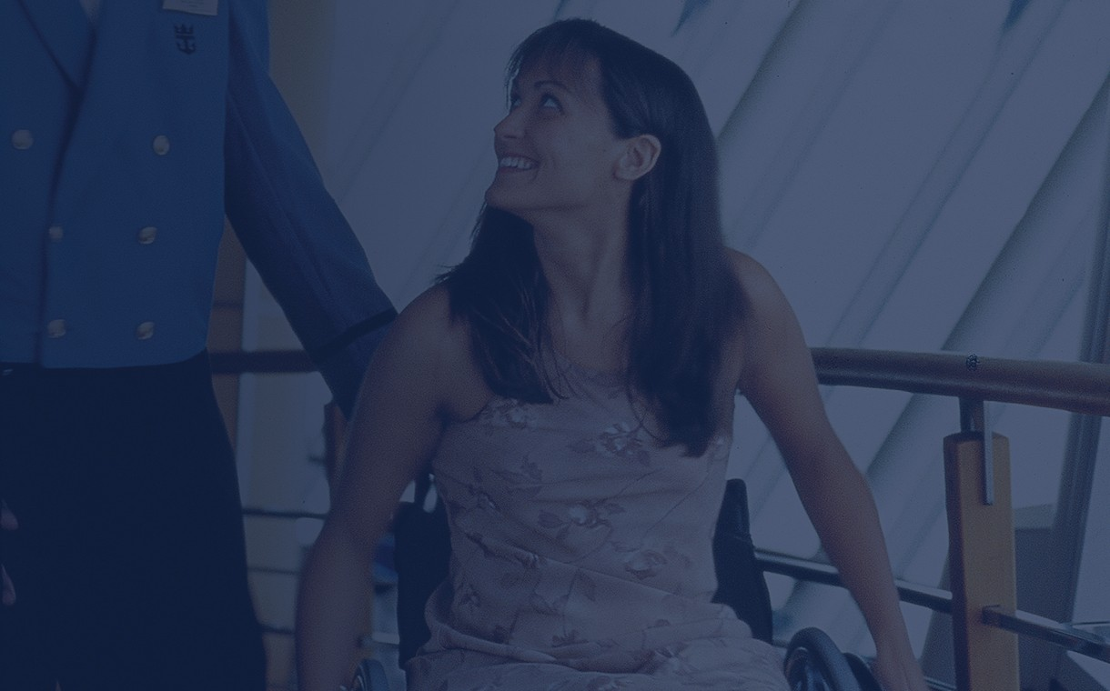 A girl in a wheelchair receiving assistant from a Royal Caribbean Cruise Line employee onboard the ship.