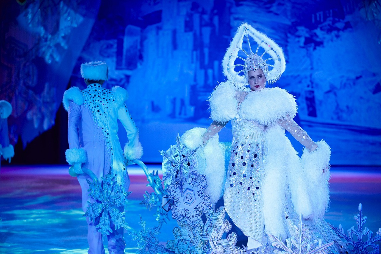 Woman performer in a white and blue snowflake costume during the Frozen in Time ice skating show on Oasis.